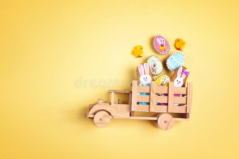 Träleksaklastbil med hemlagade pepparkakakakor för påsk i baksidan på gul bakgrund Rolig påskgarnering royaltyfri foto