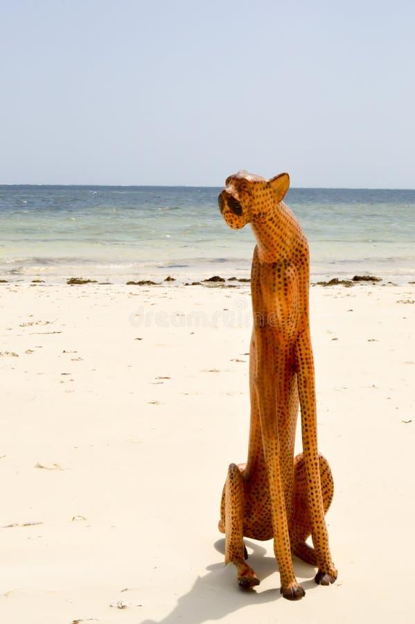 Träleopard på stranden royaltyfri bild