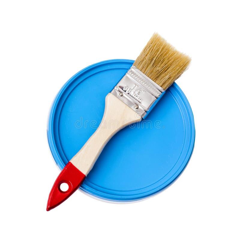 Trämålarfärgborste på en blå målarfärghink Isolat på vitbakgrund arkivbild