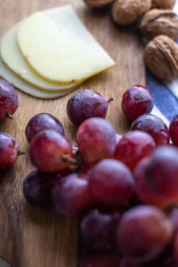 Trämagasin med druvor och ost arkivbilder