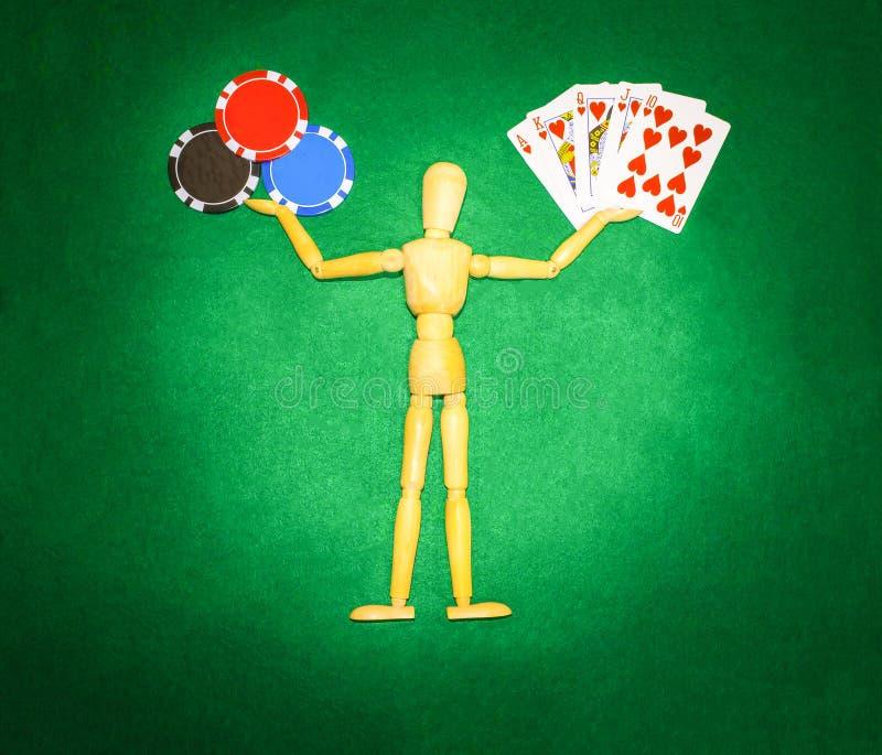 Trämannen med händer rymmer upp till chiper och kort för att spela poker arkivbilder