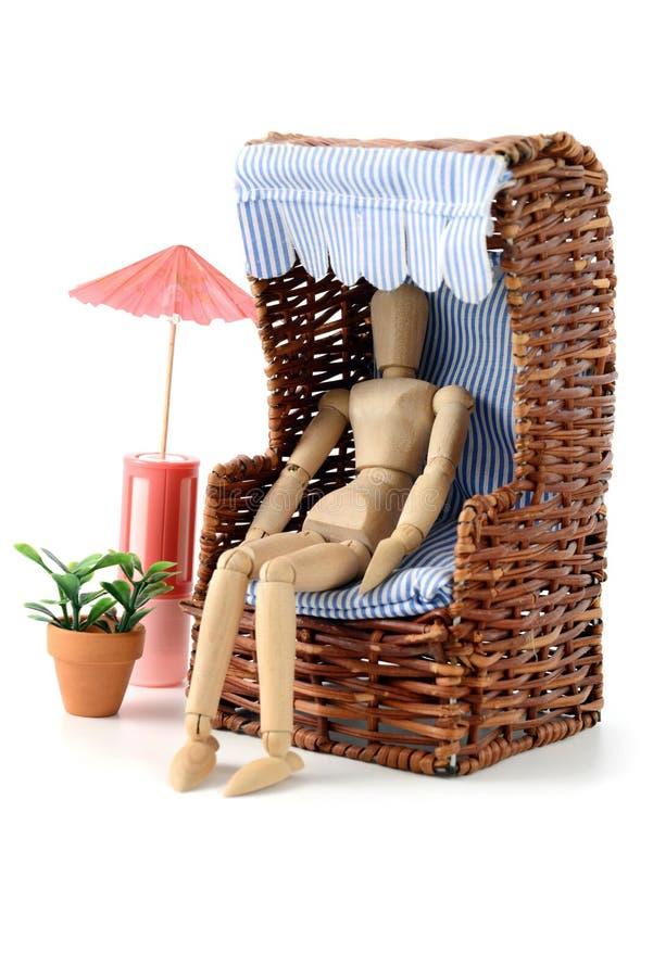 Trämannequines som solbadar i trädgård med stol- och strandcha royaltyfri bild