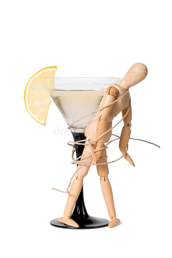 Trämannikin som fästas till exponeringsglaset av vermut Begrepp av berusning, alkoholmissbruk royaltyfri bild