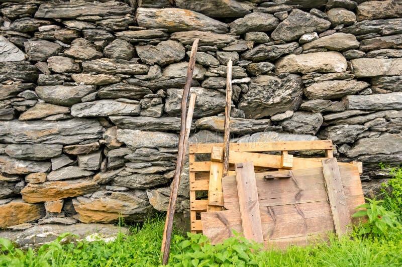 Trämaterial som lutar på en stenvägg arkivfoto