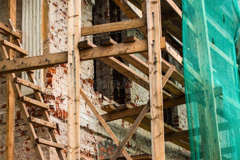 Trämaterial till byggnadsställning nära den gamla byggnaden och ett skyddande ingrepp royaltyfri foto