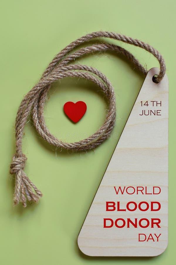Trämedalj med hjärta som begrepp för världsblodgivaredag royaltyfria bilder