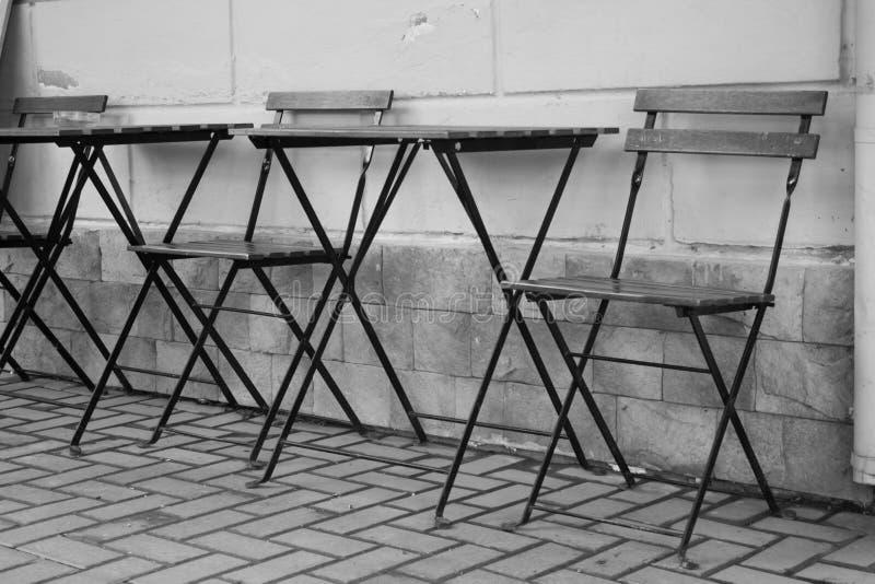 Trämetalltabeller och stolar på trottoaren på bakgrundsväggen royaltyfri bild