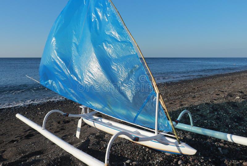 Trämodellen av en traditionell fiskebåt kallade jukung med bambuflöten, och blått seglar Litet fartyg på stranden med svart sand arkivfoto