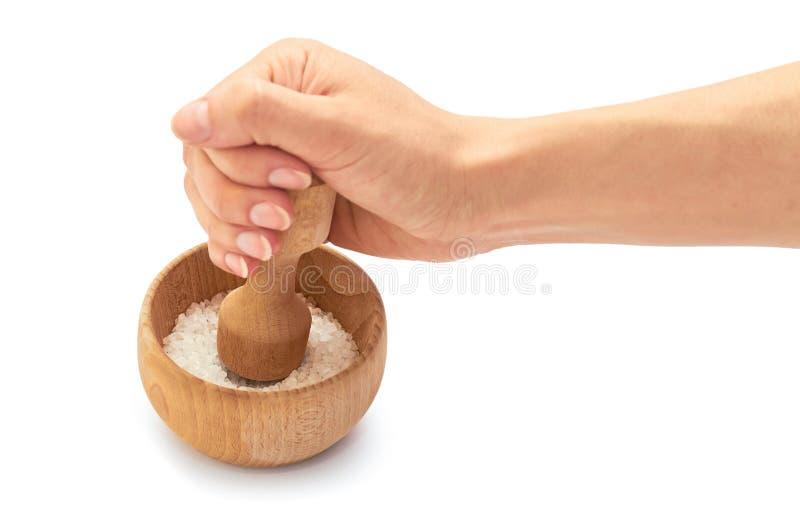 Trämortel för kvinnligt handbruk med havet som är salt för att laga mat bakgrund isolerad white arkivfoton