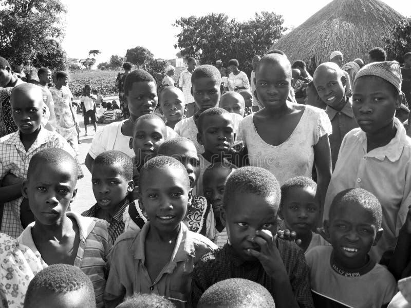 Tränga ihop afrikanska nyfikna barn som samlar, som hjälpmedellättnadsarbetare ankommer arkivfoto