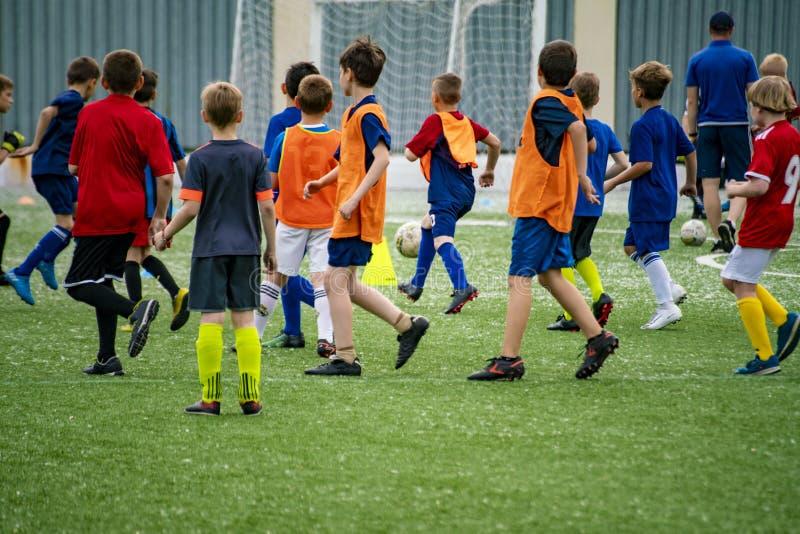 tränga ihop många barnungar som spelar fotboll på gräsfältet på stadiorna arkivfoton