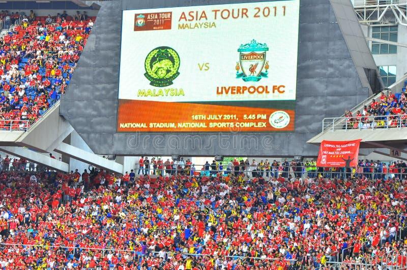Tränga ihop på stadionen med den stora skärmen i bakgrunden royaltyfri bild