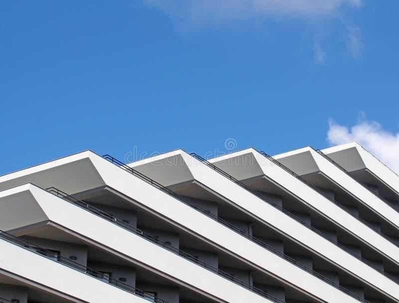 Tränga någon detaljer av diagonala geometriska balkonger för ett geometriskt vitt modernt flerfamiljshus och räcke mot en ljus bl arkivfoton
