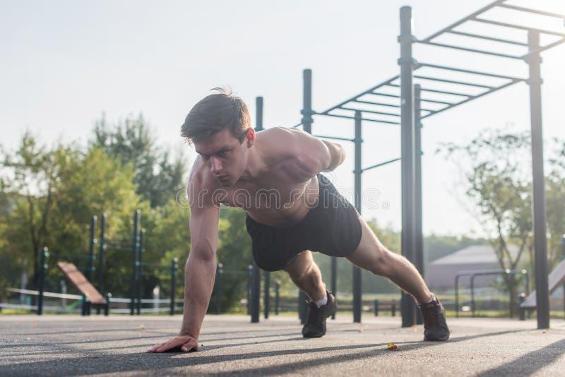 Tränga sig in den unga mannen för idrottsman nen som gör en-armen liggande armhävningövningen som utarbetar hans övrekropp, utanf royaltyfri foto