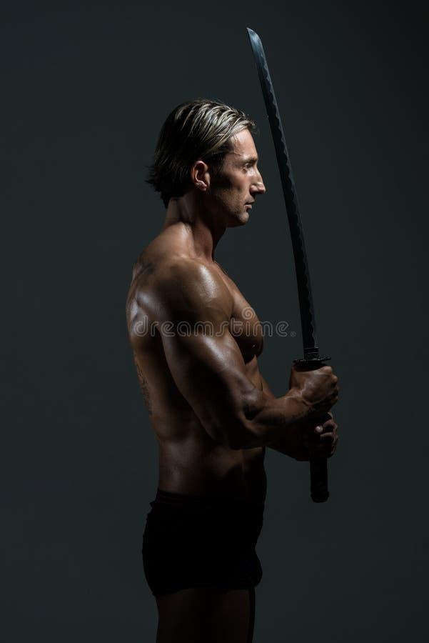 Tränga sig in manlig modell In Studio With ett svärd royaltyfri foto