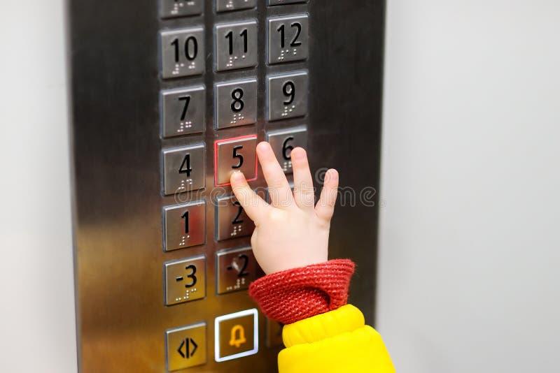 Trängande knapp för litet barn i hiss royaltyfria bilder