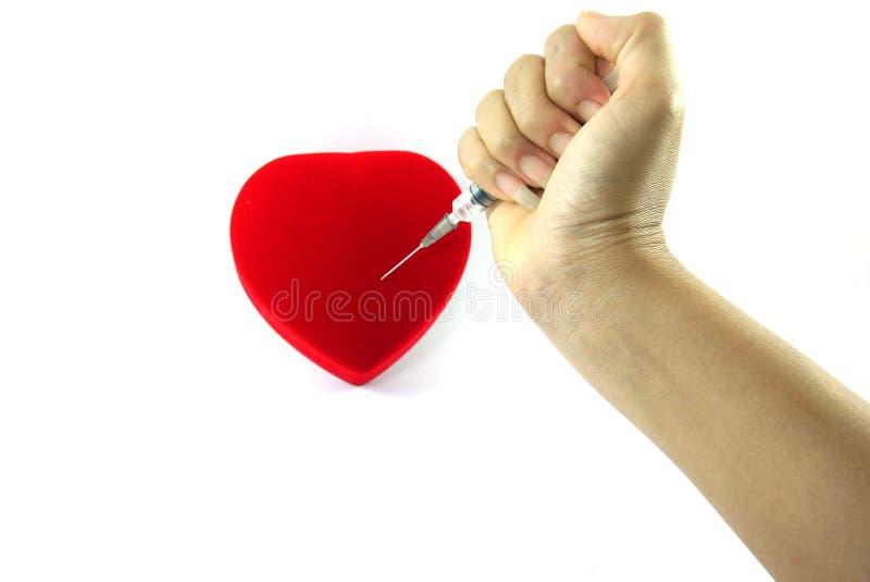Trängd igenom röd hjärta på en vit bakgrund arkivfoton