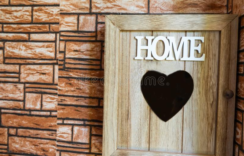 Tränyckel- ask som på rymmer väggen med hjärta i mitt Bokstäver som är hem- i vita och fyrkantiga tegelplattor på ingångarna av h royaltyfri bild