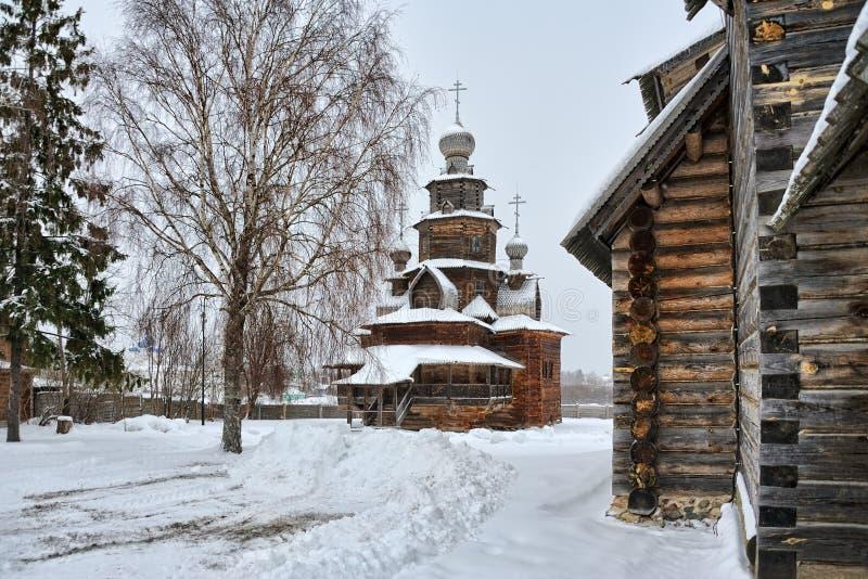 Träomgestaltningkyrka som inramas av träd och hörnet av en annan kyrka i vinter royaltyfri foto