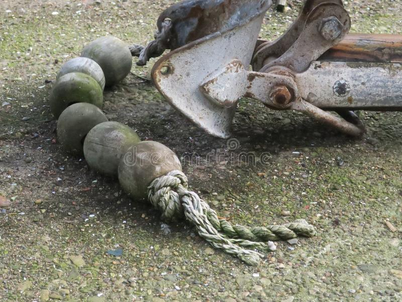Träpärlor av en gammal floater på arope som lägger på trottoaren i hamnen av Den Helder fotografering för bildbyråer