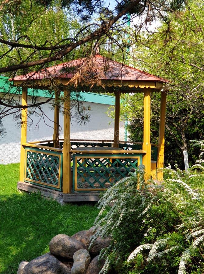 Träpergola i en dekorativ blommande vårträdgård arkivbilder