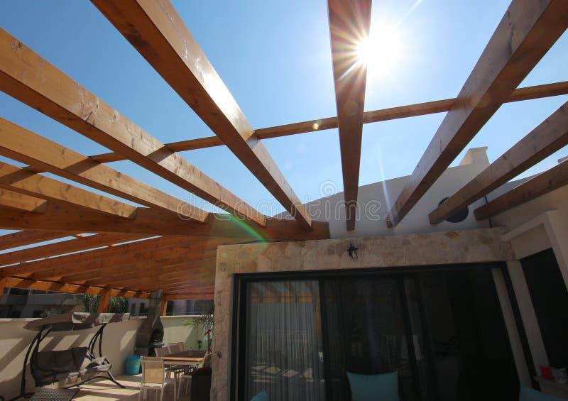 Träpergola på taket av en villa arkivfoton