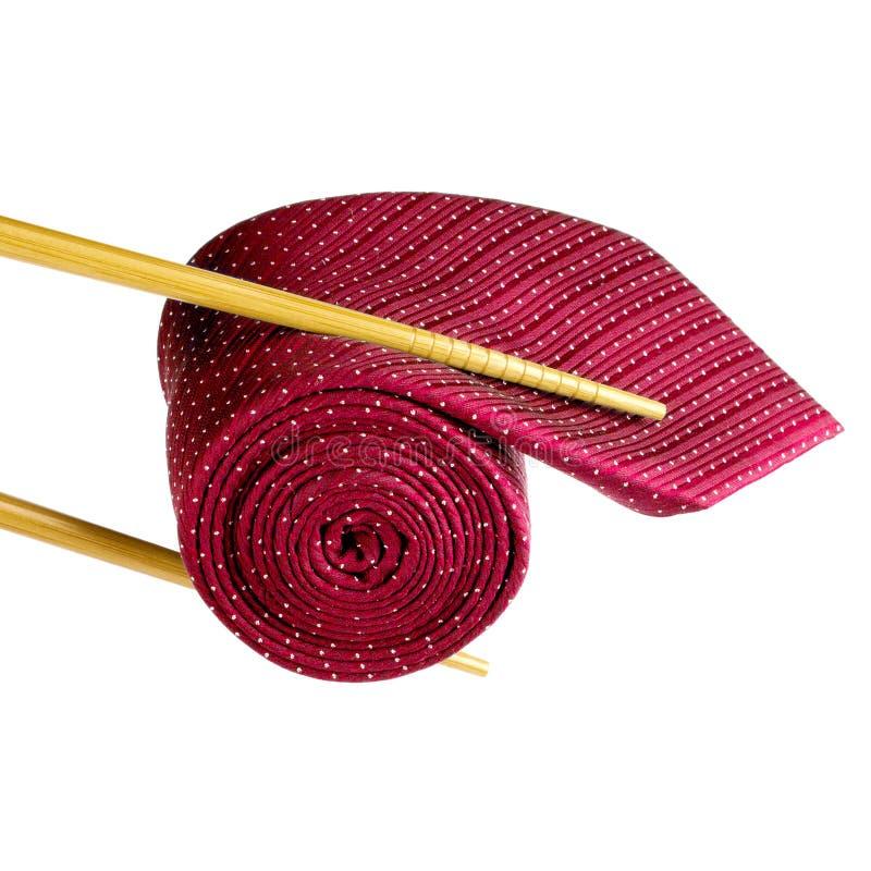Träpinnar som rymmer den röda manliga slipsen, rullade som sushi på vit bakgrund fotografering för bildbyråer