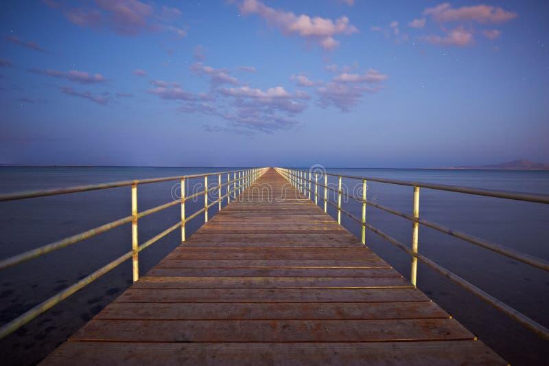 Träpir eller brygga på vatten för havssolnedgång- och himmelreflexion fotografering för bildbyråer