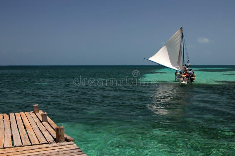 Träpir och seglingskepp, tobak Caye, Belize fotografering för bildbyråer
