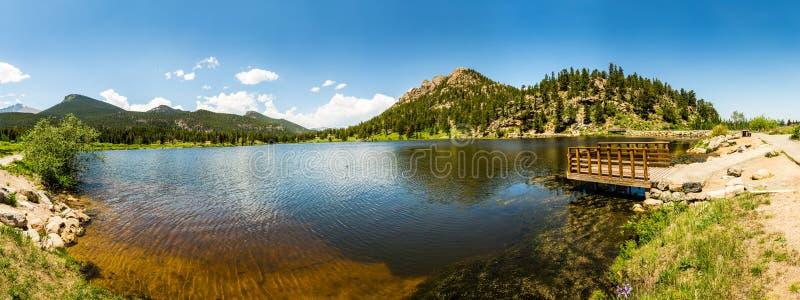 Träpir på sjön mot bergpanorama royaltyfria bilder