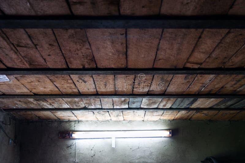 Träplankatak för gammalt seminarium med stålstrålar och ett dagsljuslysrör på en packad vägg arkivfoto