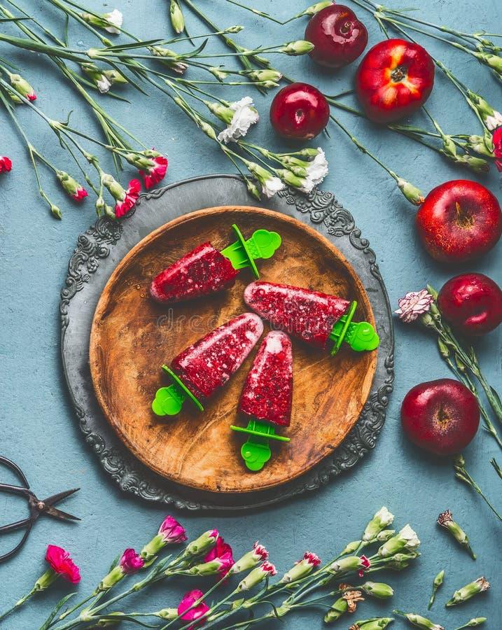 Träplatta med hemlagad röd fruktglass eller isglass fryst fruktfruktsaft på lantlig köksbordbakgrund med trädgårds- flöde arkivbild