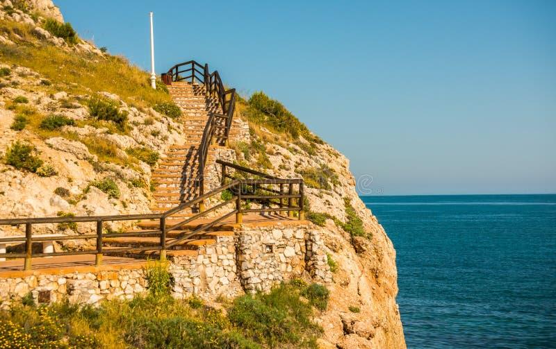 Träpromenad längs havskusten som placeras på en klippa, vaggar in arkivfoto
