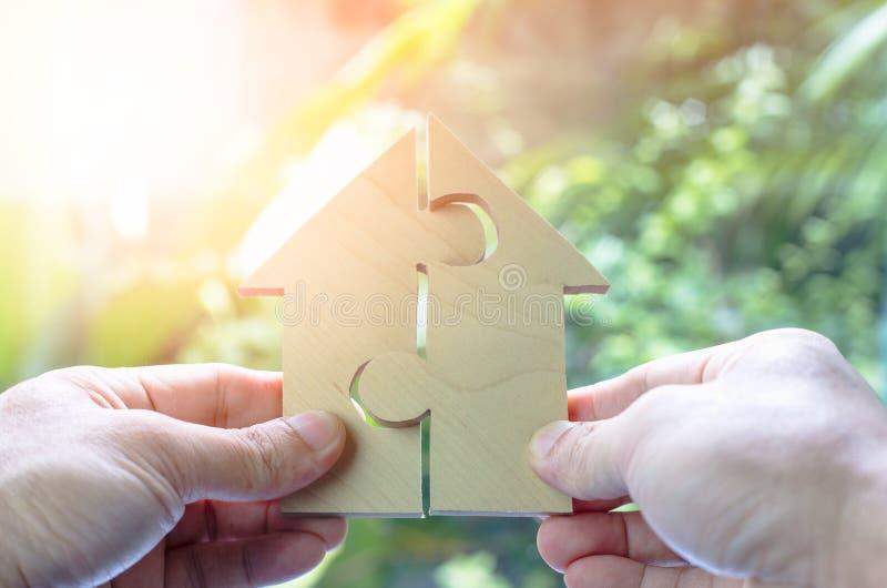 Träpusselväntan att fullgöra hem formar för den hem- byggandedrömmen, eller det lyckliga livbegreppet för egenskap, intecknar och royaltyfri foto