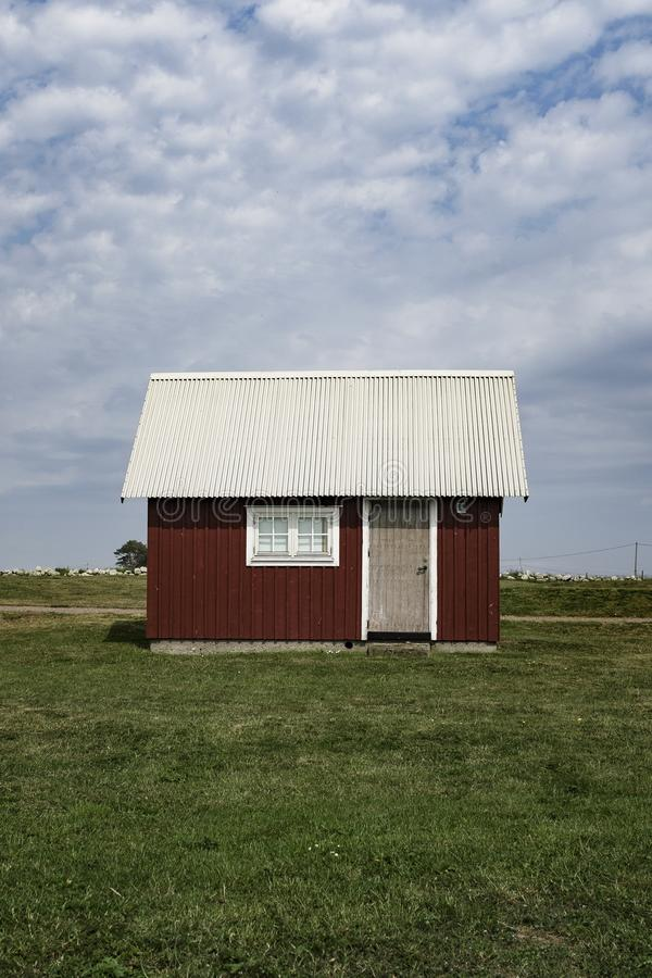 Träröd ladugård med ett vitt tak i ett stort grönt fält med molnig blå himmel arkivfoton