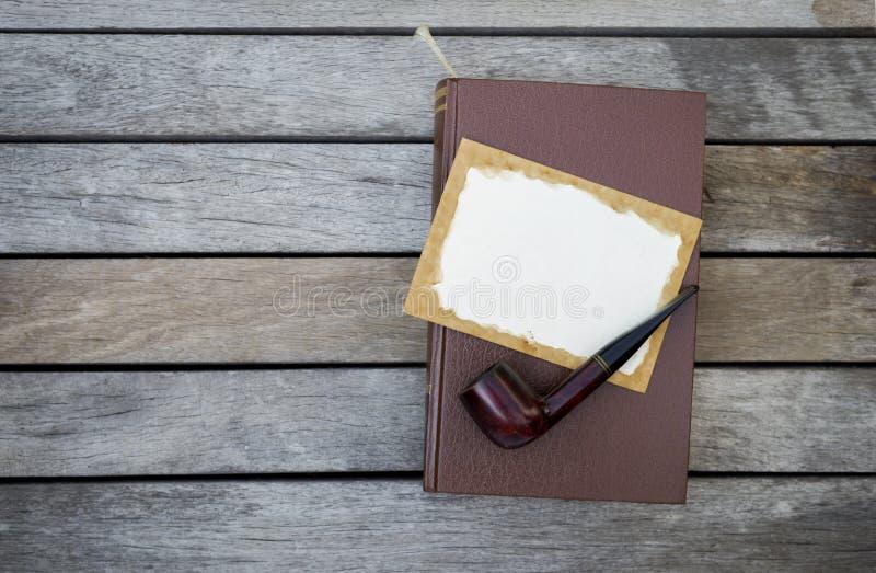 Träröret och det tomma gamla pappers- kortet på den bruna läderräkningen bokar royaltyfria foton