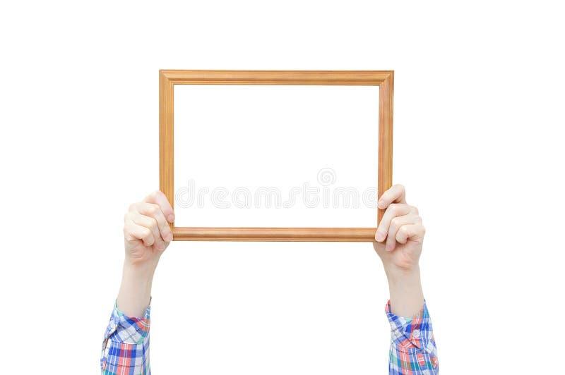 Träram för foto i händerna av en flicka Närbild vit isolat arkivbilder