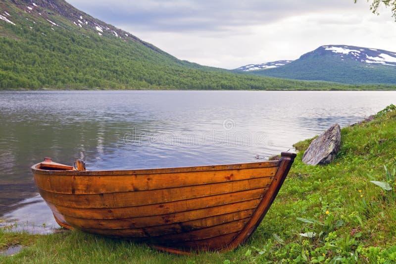 Träroboat på Lapland sjön. royaltyfri foto