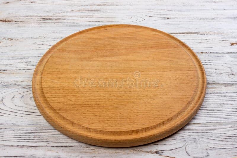 Trärunt tomt bräde för pizza på wood tabellbakgrund, bästa sikt Modellen för meny, receptet eller några besegrar Lodlinjen avbild arkivbilder