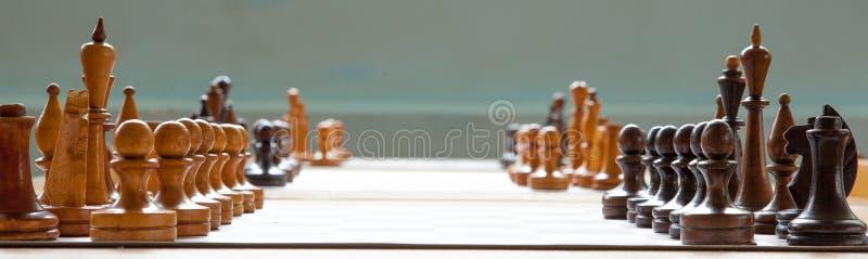 Träschackbräde med träschackstycken royaltyfri foto
