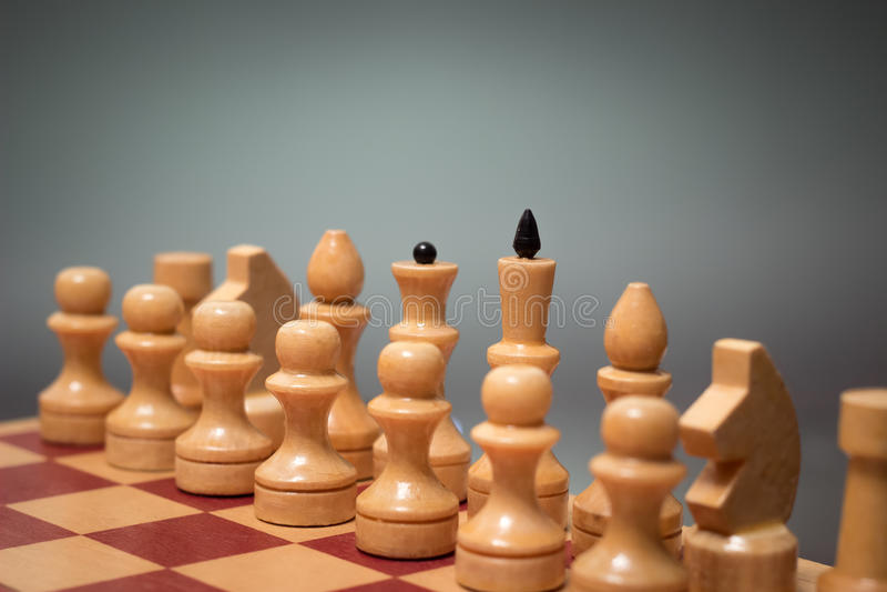 Träschackbräde och schackpjäser av vit färg på en grå bakgrund arkivbilder