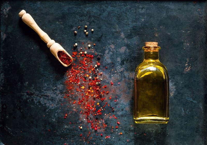 Träsked med kryddor och olivolja i en glasflaska på en bakgrund av gamla rostiga metaller, begrepp för organisk mat, arkivfoton
