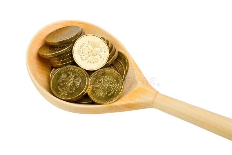 Träsked med mynt royaltyfria bilder