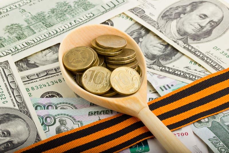 Träsked med mynt på en bakgrund av pengar royaltyfri bild