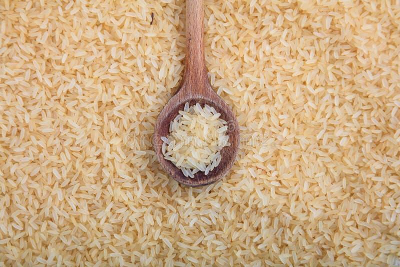 Träsked och förvälld risbakgrund royaltyfria foton