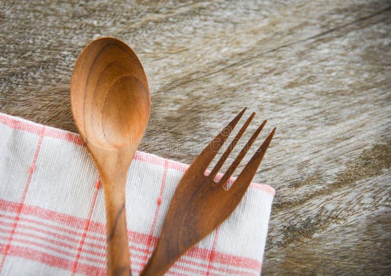 Träsked- och gaffelkitchenwareuppsättning på napery på den äta middag tabellen royaltyfri bild