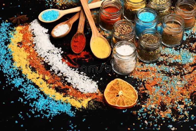 Träskedar med det salta paprika, gurkmeja och havet royaltyfria foton