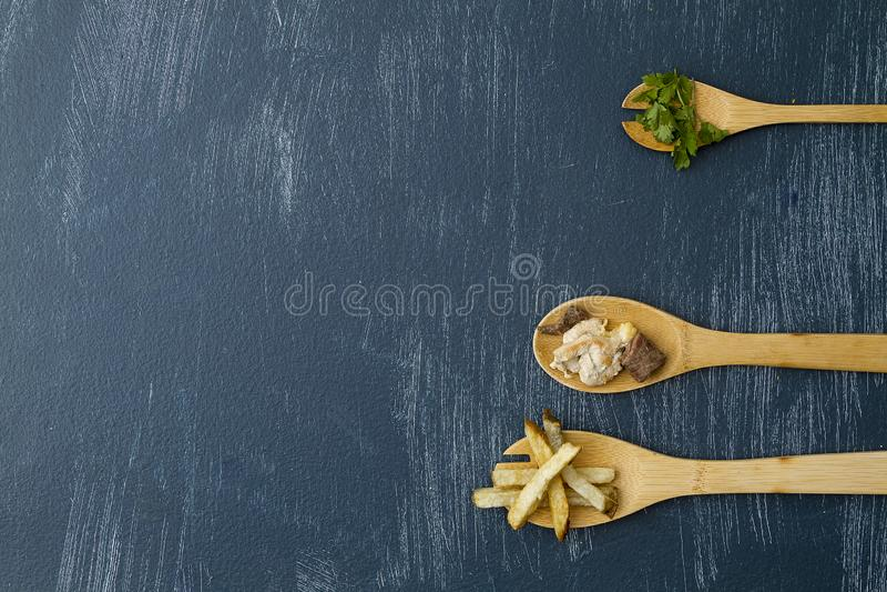 Träskedar med ingredienser som förbereder kött med potatisar och koriander arkivbilder