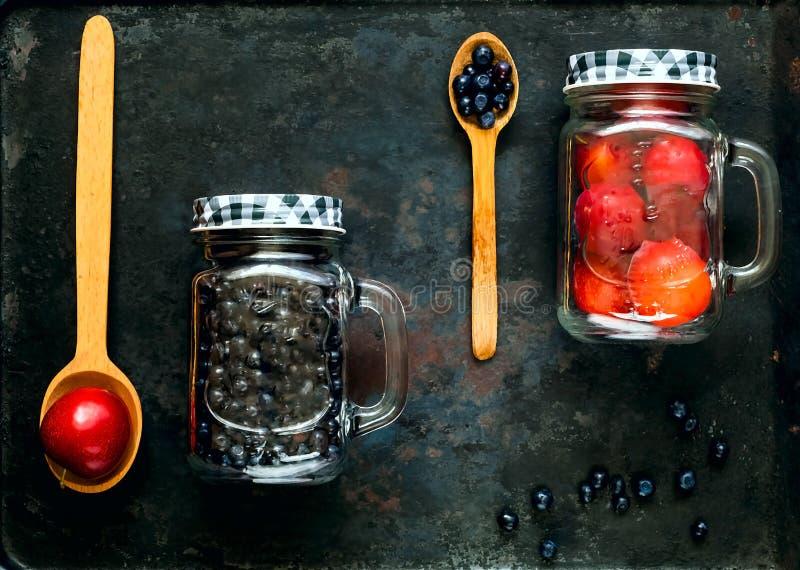 Träskedar och blandade röda frukter för bär och i den glass kruset på bakgrund av gamla rostiga metaller, begrepp av organisk mat arkivfoto