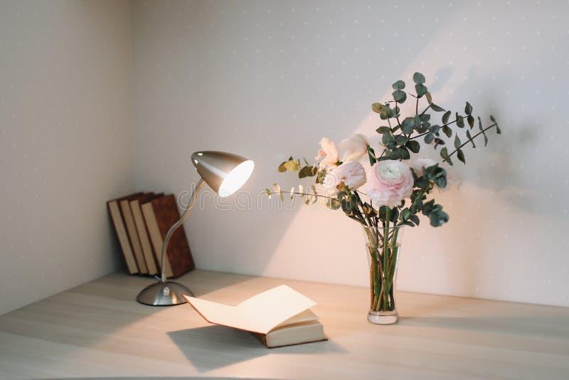 Träskrivbord med böcker och blommor Bukett och böcker på vit bakgrund Planläggnings- och designbegrepp arbetsplats royaltyfri bild